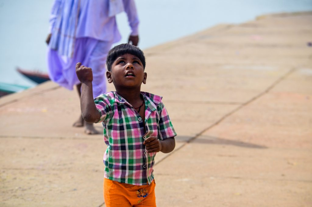 A boy flying a kite on the Ghats
